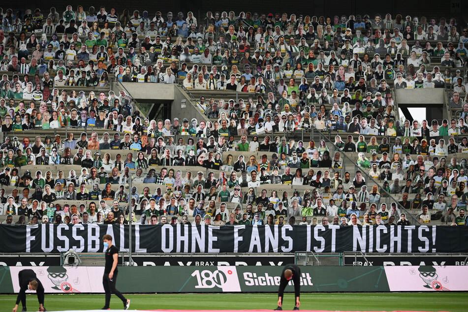"""Pappaufsteller stehen statt der Fans auf der Tribüne im Borussia-Park, an der ein Banner mit der Aufschrift """"Fussball ohne Fans ist nichts!"""" hängt."""