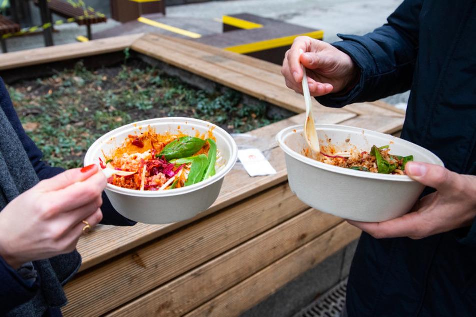 Ein Mann und eine Frau nehmen ihr Mittagessen aus einer Einwegverpackung zu sich. Durch Essenbestellungen wächst der Müllberg stetig.