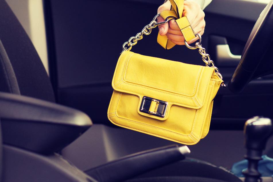 Die Autofahrerin versuchte ihre Tasche noch festzuhalten, doch der Unbekannte entriss sie ihr. (Symbolbild)