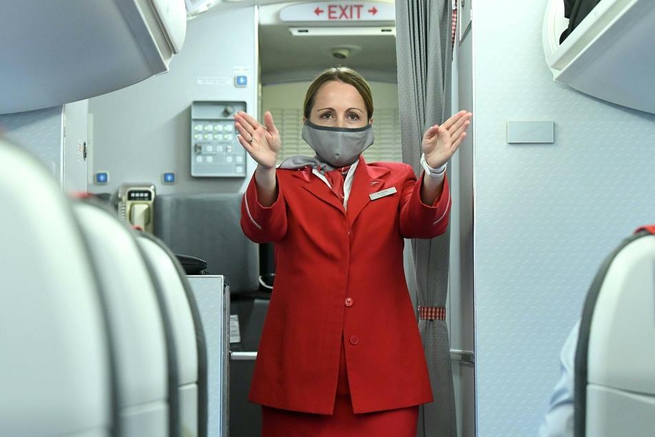 Eine Flugbegleiterin mit Mundschutz gibt Sicherheitseinweisungen in einem Flugzeug der Austrian Airlines (AUA).