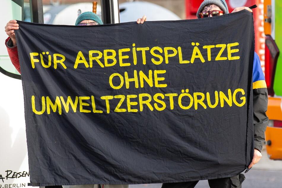 """Umweltaktivisten halten in Weißwasser ein Banner mit der Aufschrift """"Für Arbeitsplätze ohne Umweltzerstörung"""" in die Höhe. Das dürfte auch eine Devise des Strukturwandels in der Lausitz sein."""