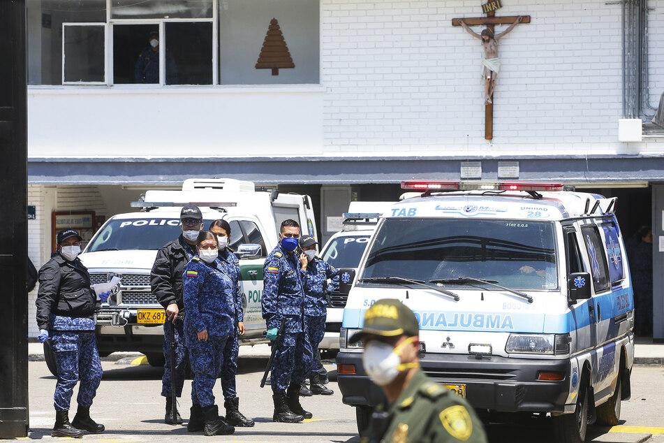 """Polizei und Gefängniswärter stehen neben Krankenwagen im Gefängnis """"La Modelo""""."""