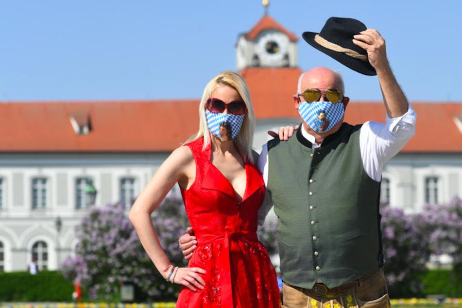 """Der Geschäftsführer von Angermaier Trachten, Axel Munz, und seine Freundin Yvonne """"Y.V.E."""" Marwan tragen blau-weiße Trachtenmasken mit König Ludwig- und Sissy-Motiven vor der Schlossanlage des Schloss Nymphenburg."""