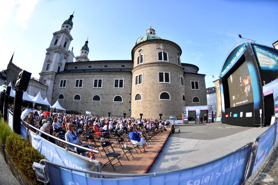 """Besucher sitzen anlässlich der Eröffnung der Salzburger Jubiläumsfestspiele 2020 während der Freiluft-Übertragung der Premiere der Oper """"Elektra"""" von Strauss in der Felsenreitschule auf dem Kapitelplatz."""