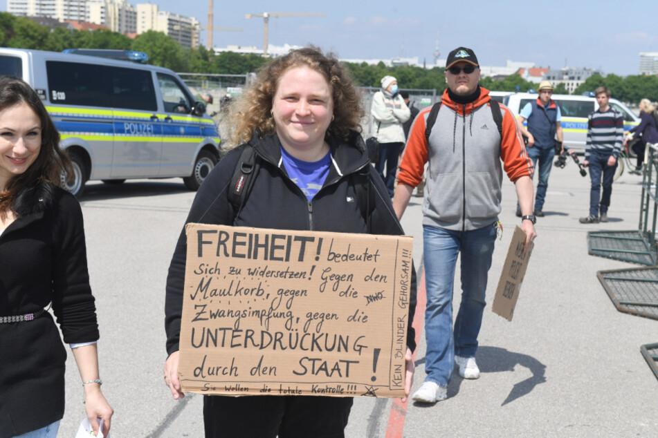 """Eine Demonstrantin trägt ein Schild mit der Aufschrift """"Freiheit bedeutet sich zu widersetzen! gegen ......"""" und kommt damit auf die Theresienwiese."""