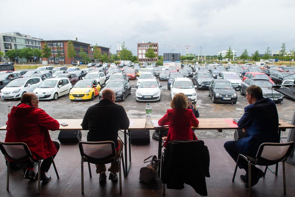 Das Präsidium sitzt auf der Bühne, während im Hintergrund die Delegierten in ihren Autos sitzen.