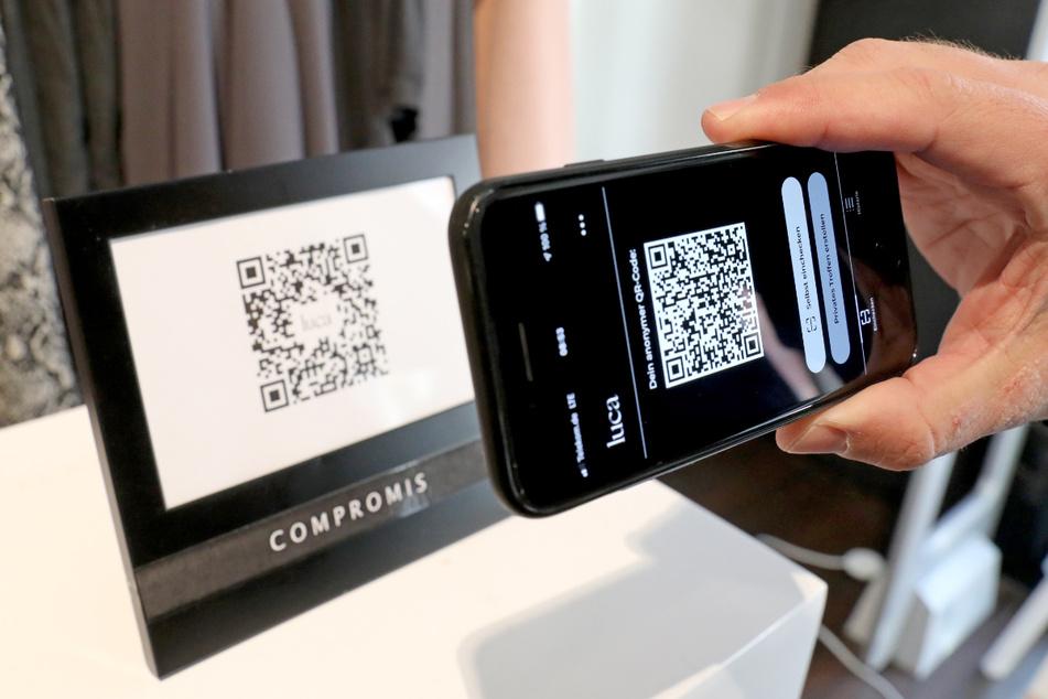 Ein Mann checkt über die App den Code eines Geschäfts.