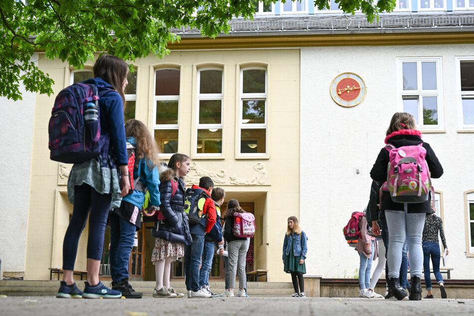 Schülerinnen und Schüler einer vierten Klasse stehen mit Abstand auf einem Schulhof. (Archivbild)