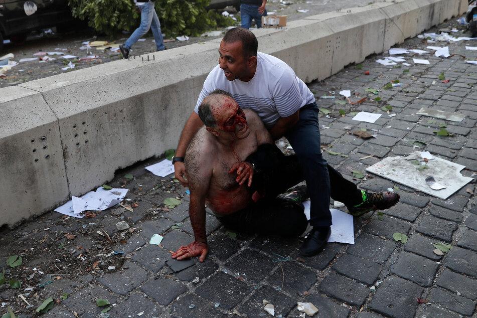 Ein Mann hilft nach einer Explosion in Beirut einem Verletzten auf einer Straße. In der libanesischen Hauptstadt ist es zu einer schweren Explosion gekommen.