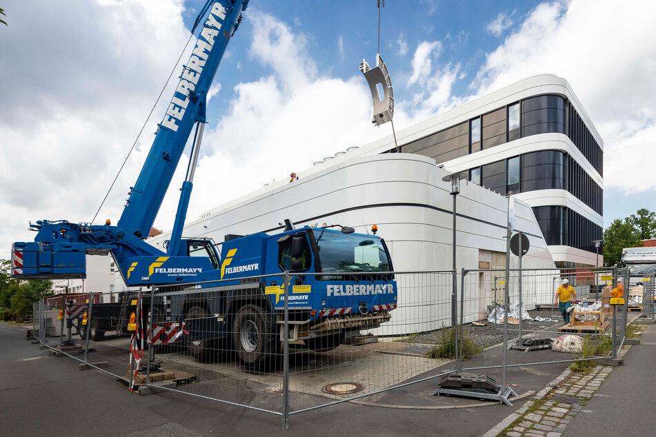 Durch die geöffnete Decke schweben die einzelnen Teile des 16 Tonnen schweren Geräts ins Gebäude.