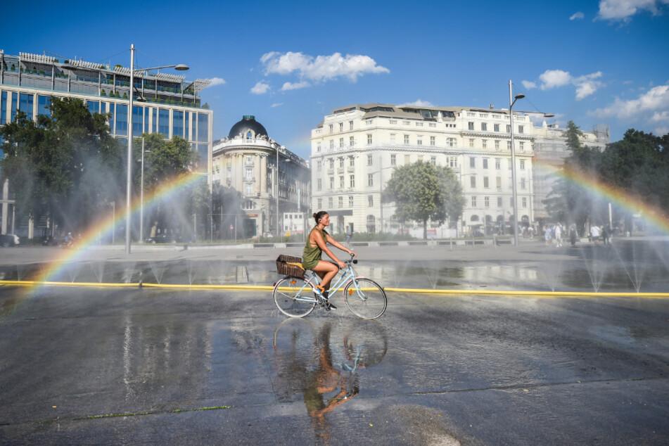 Österreich, Wien: Ein Radfahrerin kühlt sich in der Nähe einer Wasserinstallation auf dem Schwarzenbergplatz ab.