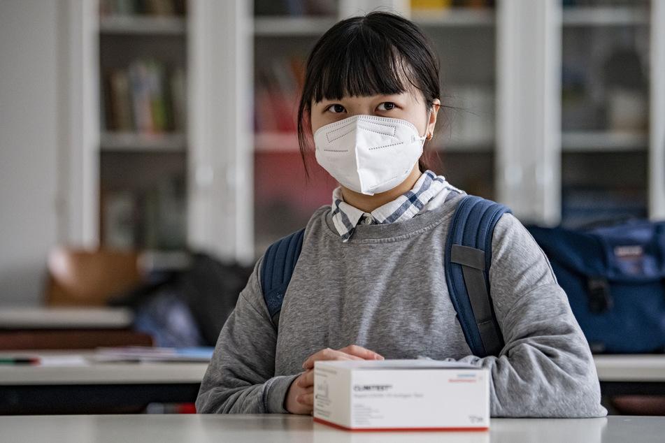 Eine Schülerin sitzt mit einem Corona-Selbsttest in einem Klassenraum. Niedersachsen will die Testfrequenz nach den Sommerferien erhöhen. (Symbolfoto)
