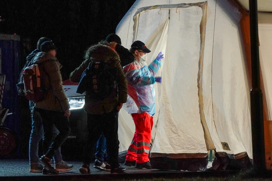 Ein medizinischer Helfer (r.) bringt Schüler in ein Untersuchungszelt auf einem Schulgelände.