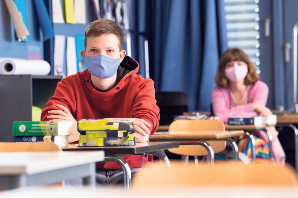 Ein Schüler nimmt mit Maske am Unterricht teil. Der Schulalltag unter Pandemiebedingungen ist eine Herausforderung für alle Beteiligten.