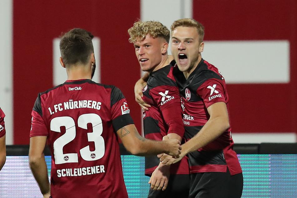 Robin Hack (M.) jubelt mit seinen Nürnberger Kollegen Fabian Schleusener (l.) und Tim Handwerker über seinen Treffer zum 1:0.