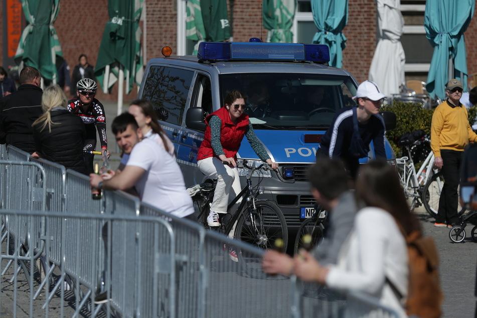 Ein Polizeiwagen fährt zwischen vielen Menschen am Düsseldorfer Rheinufer Streife.
