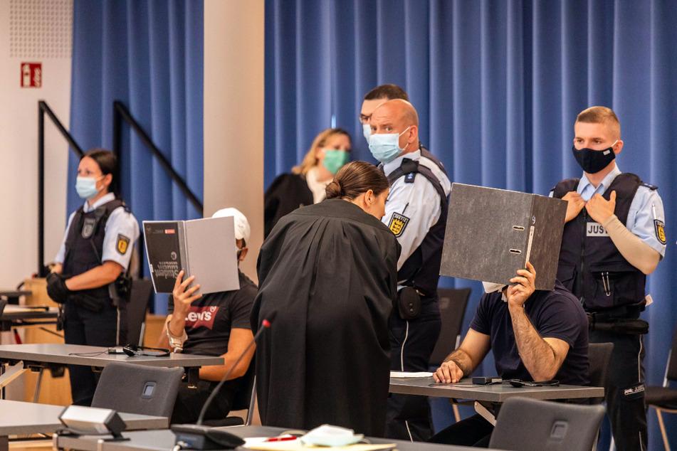 Zwei Angeklagte halten Mappen als Sichtschutz vor ihre Gesichter, während eine Verteidigerin sich mit dem rechten Angeklagten bespricht.