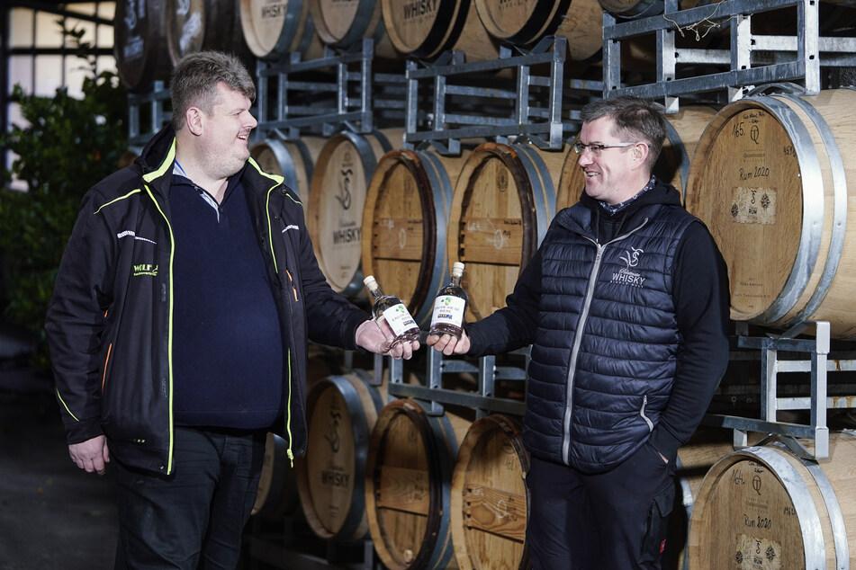 Sippel (r.) und Lenhardt stehen vor Whiskyfässern und halten Flaschen mit zum Whisky gebrannten Bier in den Händen.