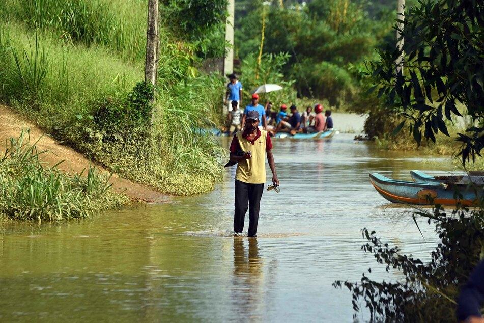 """Ein Mann watet durch eine Straße, die zuvor durch die heftigen Regenfälle des Zyklons überflutet worden ist. Mitten in der Corona-Pandemie hat einer der stärksten Stürme der Region in der jüngeren Geschichte unter anderem auch Indien und Bangladesch getroffen. Wirbelsturm """"Amphan"""" hat zahlreiche Menschen das Leben gekostet."""