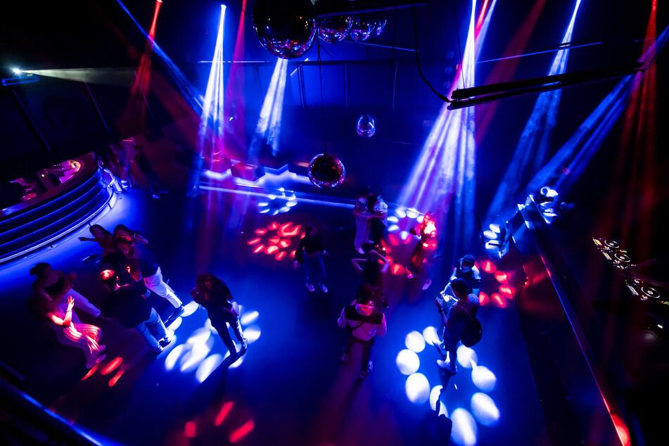 Junge Menschen feiern in einer Diskothek auf der Tanzfläche.