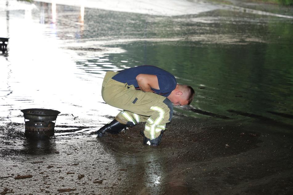 Die Kameraden der Feuerwehr mussten die verstopften Gully-Deckel anheben, damit die Wassermassen abließen konnten.