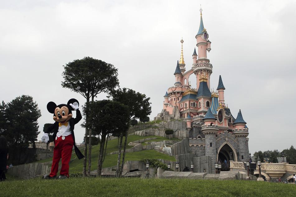 Paris: Ein als Mickey Maus verkleideter Mitarbeiter steht vor der Kulisse des Dornröschen-Schlosses im Disneyland Paris. Europas meistbesuchter Freizeitpark wird vier Monate nach seiner coronabedingten Schließung wieder teilweise für Besucherinnen und Besucher geöffnet.