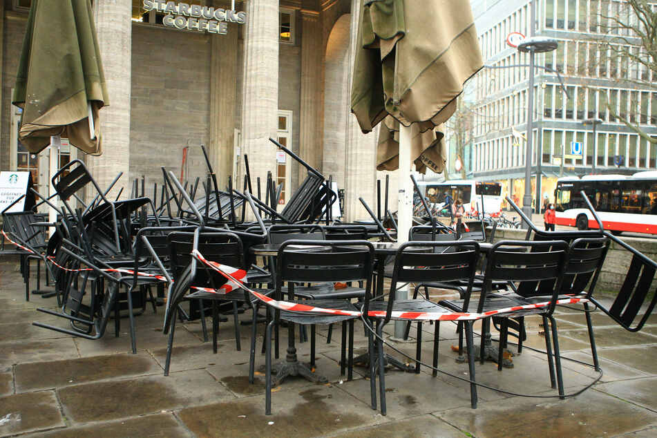 """A tape surrounding chairs and tables at a Starbucks, emblematic for the """"new normal"""" of the pandemic."""