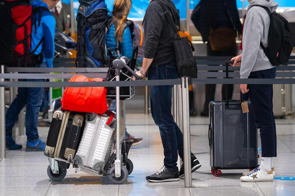 Reisende stehen am Flughafen München mit ihren Koffern an einem Check-In Schalter.