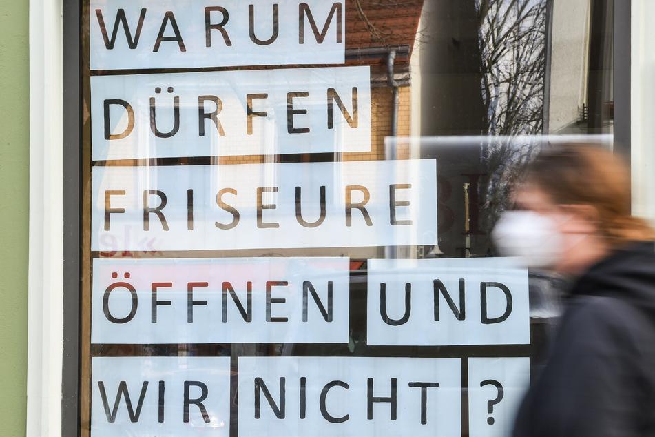 """Berlin: An dem Schaufenster eines Bekleidungsgeschäfts in Berlin Friedrichshagen steht die Frage """"Warum dürfen Friseure öffnen und wir nicht?""""."""