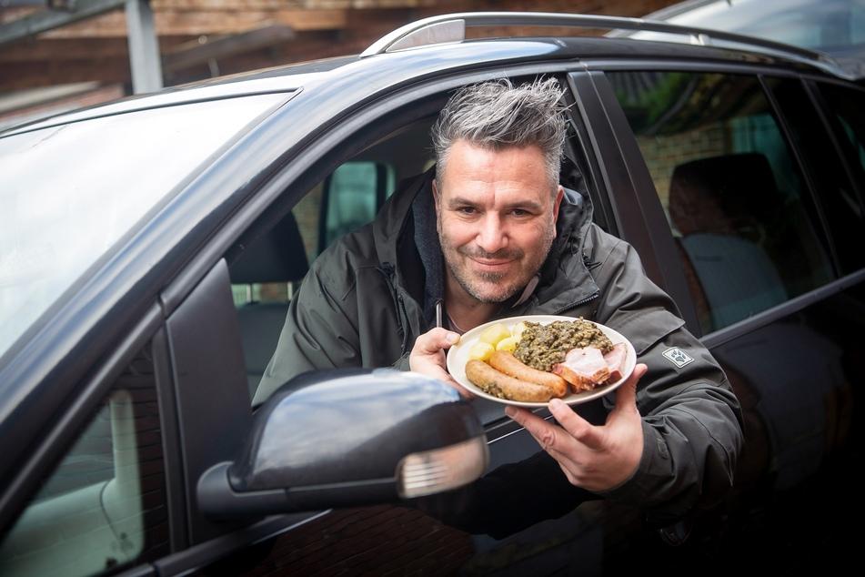 Marco Tienz (47), Grünkohltaxi-Betreiber, sitzt mit einem Grünkohlteller in seinem Auto.