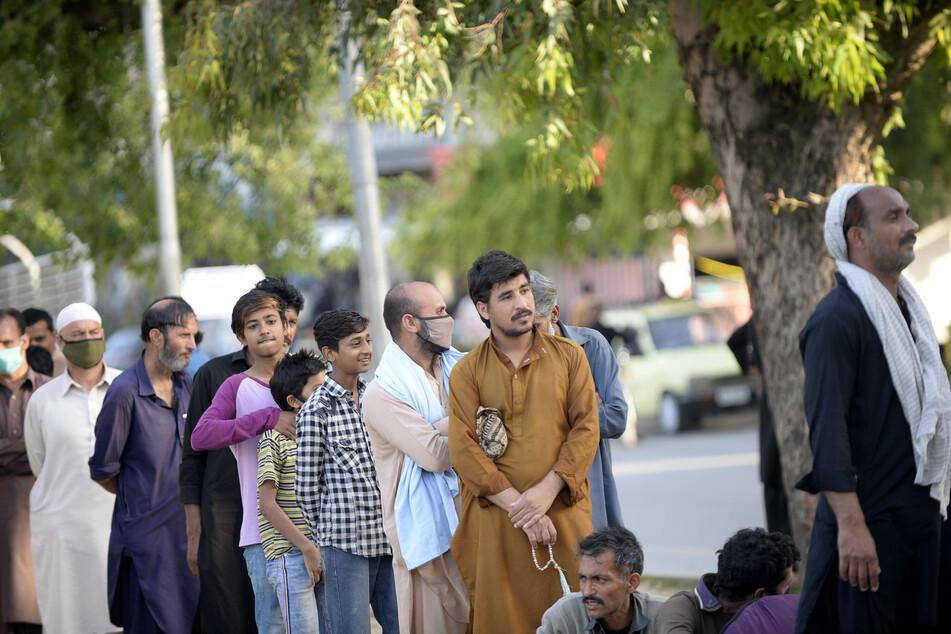Menschen in Islamabad warten auf die Verteilung von Nahrungsmitteln durch eine pakistanische Wohltätigkeitsorganisation.