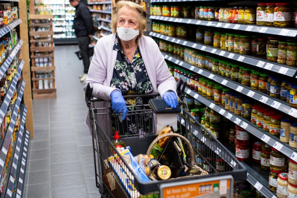 Die Maske bleibt: Beim Einkaufen muss man weiterhin den lästigen Nase-Mundschutz tragen.