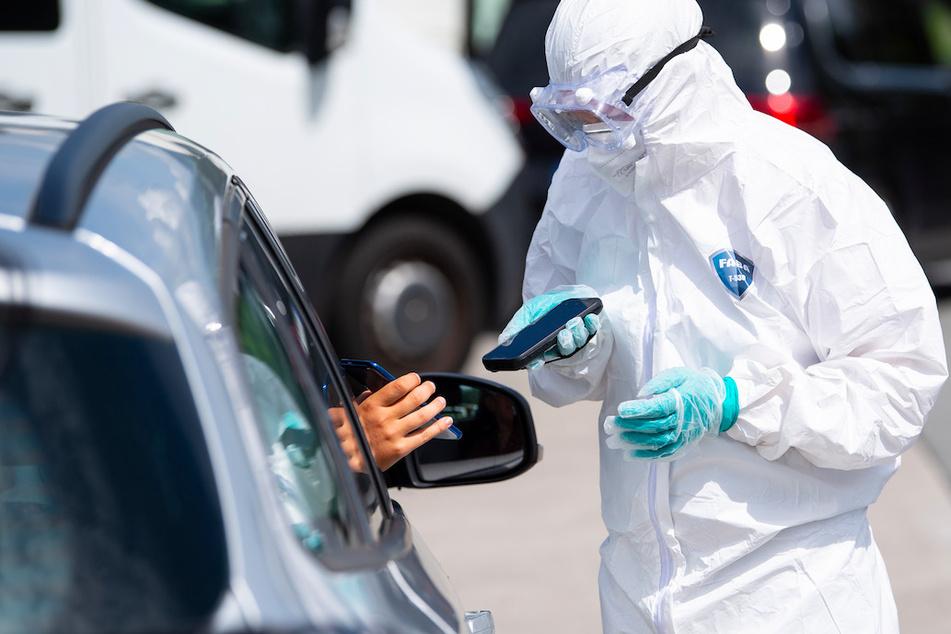 Ein Mitarbeiter der Firma Eurofins hält an einem Corona-Testzentrum einen Scanner in den Händen.