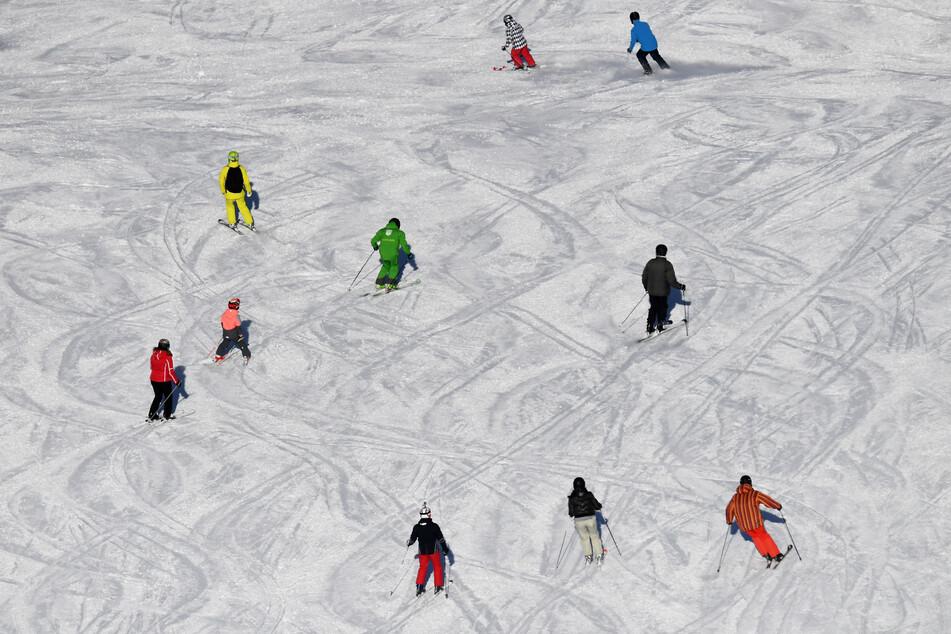 Skifahrer sind bei Sonnenschein auf einer Skipiste unterwegs.