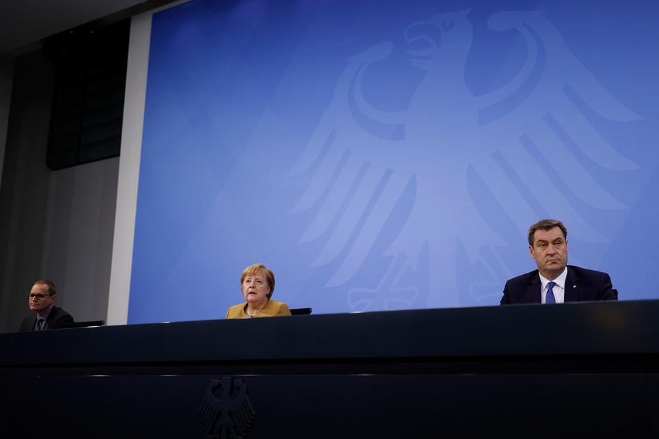 Bundeskanzlerin Angela Merkel (CDU) spricht im Bundeskanzleramt in der Pressekonferenz neben Bayerns Ministerpräsident Markus Soeder (CSU, r.) und Berlins Regierendem Bürgermeister Peter Müller (SPD, l.).