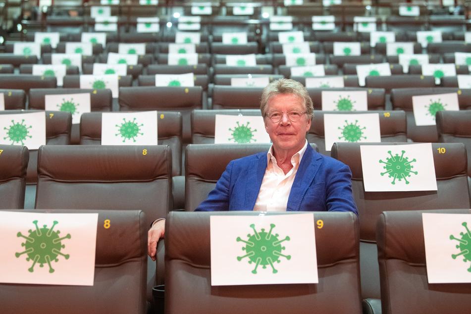 Hans-Joachim Flebbe sitzt in einem Kinosaal vom Kino Astor Grand Cinema, in dem mit Zetteln mit aufgedrucktem angedeuteten Virus-Symbol einzelne Sitzplätze abgesperrt sind.