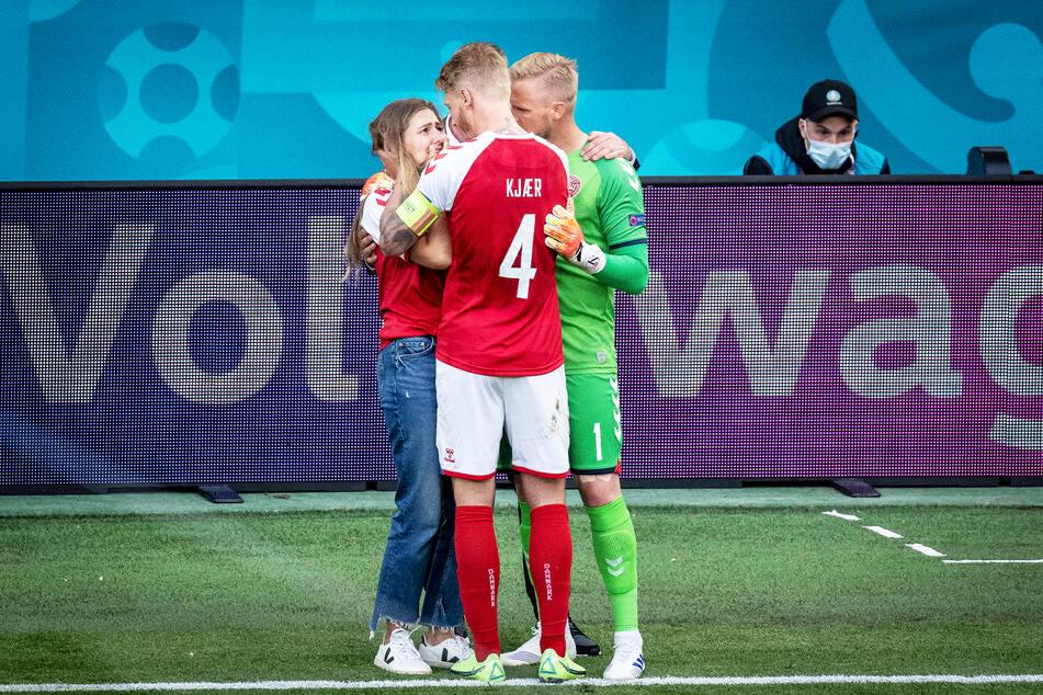 Simon Kjaer (32, M.) und Kasper Schmeichel (34) trösten Eriksens Freundin Sabrina Kvist Jensen am Spielfeldrand.