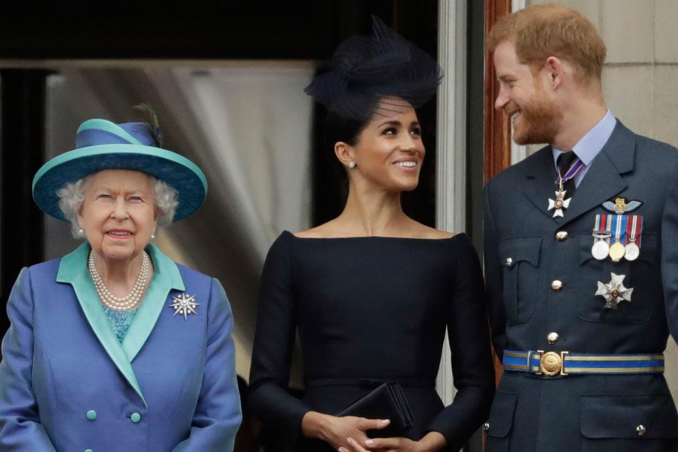 Das waren noch Zeiten: Die britische Königin, Queen Elizabeth II., ihr Enkel, Prinz Harry und seine Frau, Herzogin Meghan, stehen im Juli 2018 beim Vorbeiflug von Flugzeugen der Royal Air Force über den Buckingham-Palast auf einem Balkon.