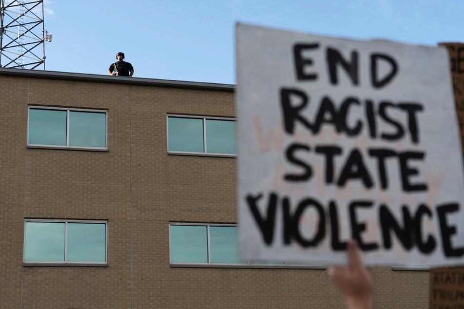 """Ein Polizeibeamter steht am Samstag auf dem Dach einer Polizeidienststelle in Aurora, während bei einer Demonstration gegen den Tod von Elijah McClain ein Plakat mit der Aufschrift """"End Racist State Violence"""" (""""Beendet rassistische staatliche Gewalt"""") in die Höhe gehalten wird. McClain starb Ende August 2019, nachdem er auf dem Weg zu seiner Wohnung von drei Polizisten von Aurora angehalten wurde."""