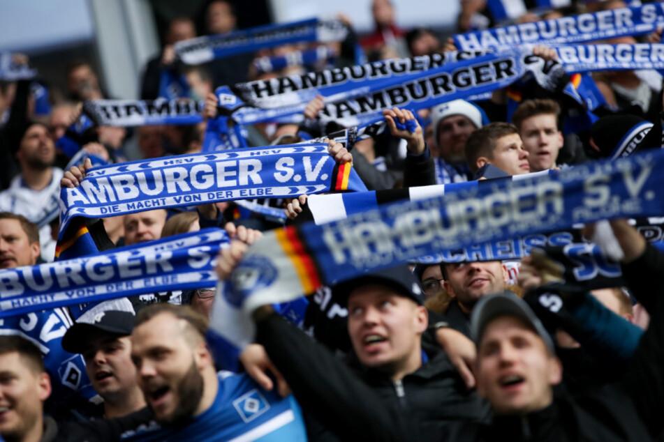 Fans des Hamburger SV halten ihre Fanschals und singen vor dem Anpfiff.