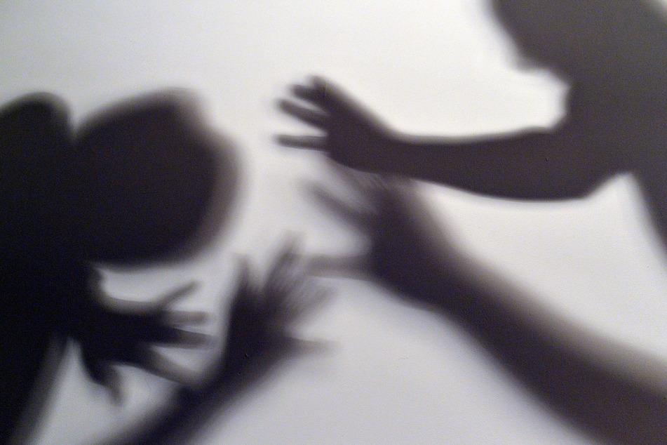 Das gestellte Bild zum Thema häusliche Gewalt symbolisiert, wie eine Frau versucht, sich vor der Gewalt zu schützen.