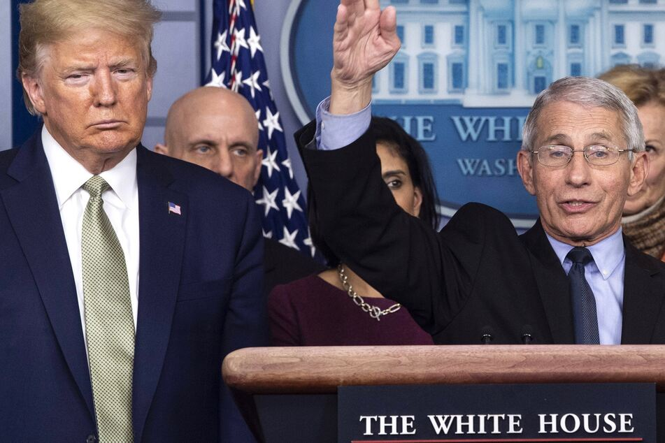President Donald Trump looking on as Dr. Anthony Fauci speaks at the White House.