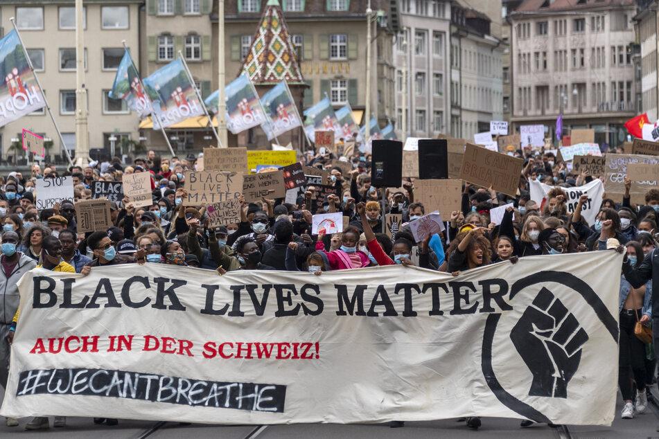 """Demonstrierende halten ein Banner mit der Aufschrift """"Black Lives Matter - Auch in der Schweiz!"""" während eines Protests gegen Rassismus und Polizeigewalt."""