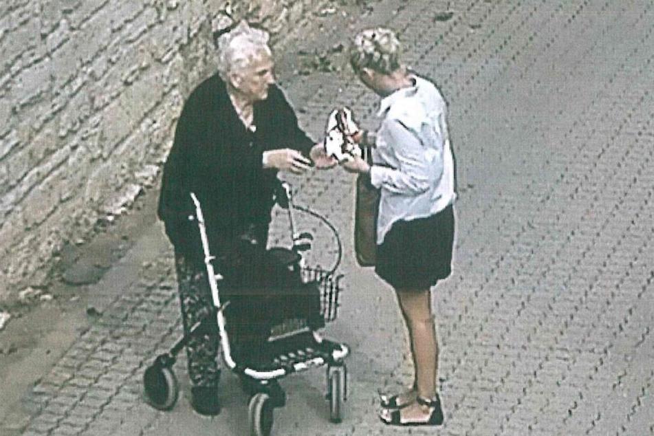 Die 80-Jährige übergibt das Geld an die Frau.
