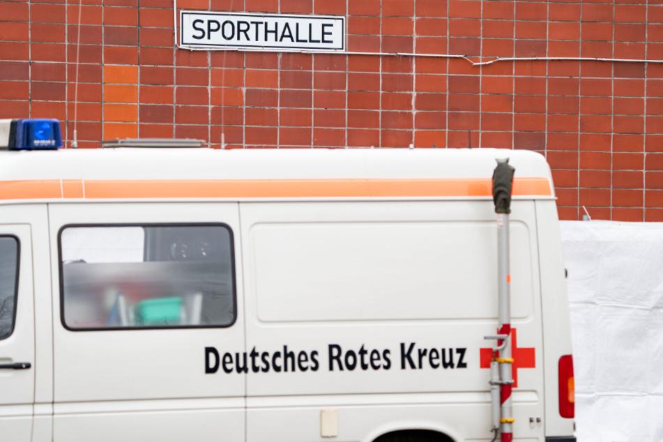 Ein Fahrzeug des Roten Kreuzes steht vor einer Sporthalle.
