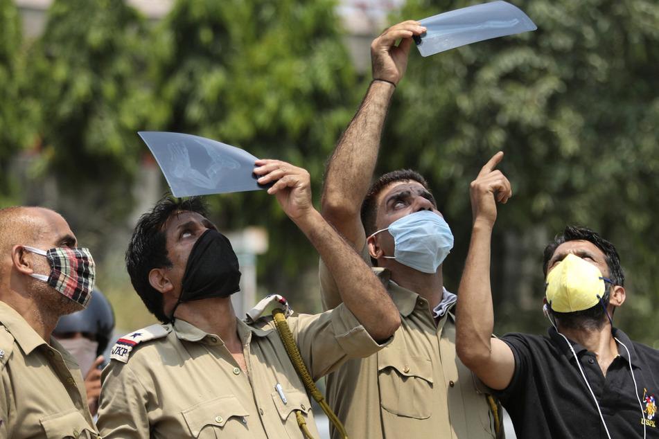 Indien, Jammu: Männer, die als Schutzmaßnahme gegen das Coronavirus Mundschutze tragen, beobachten in Jammu eine partielle Sonnenfinsternis durch Röntgenaufnahmen hindurch, um die Augen vor Strahlung zu schützen.