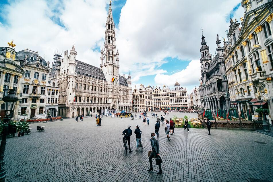 Touristen und Passanten sind auf dem Grand-Place, den zentralen Platz von Brüssel, unterwegs.