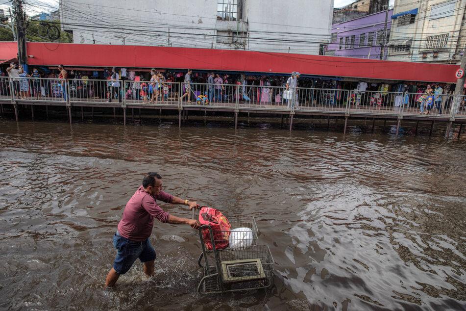 Ein Mann schiebt einen Einkaufswagen durch eine überschwemmte Straße.