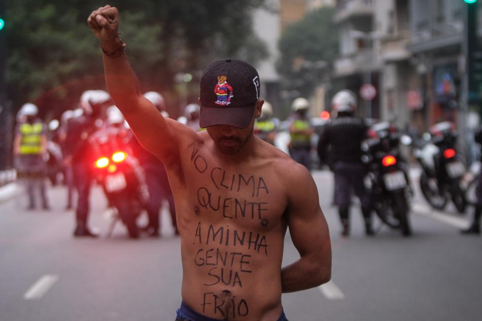 Ein Demonstrant streckt während eines Protestmarschs gegen Rassismus und den brasilianischen Präsidenten seine Faust in die Höhe.