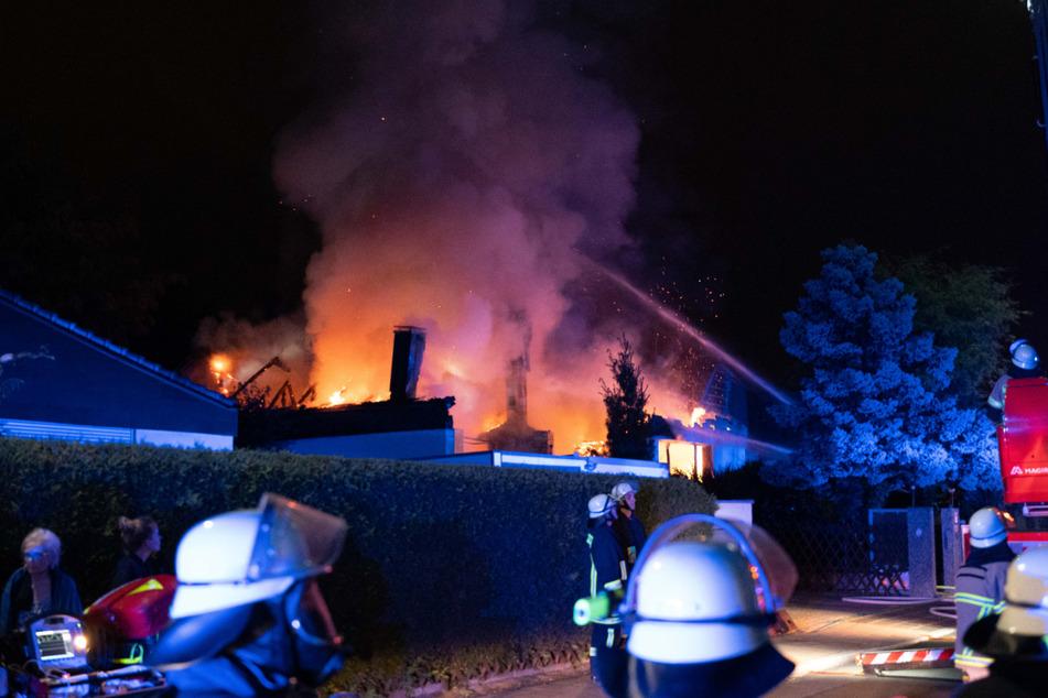 Feuerwehrleute stehen vor dem brennenden Gebäude in Fürth.